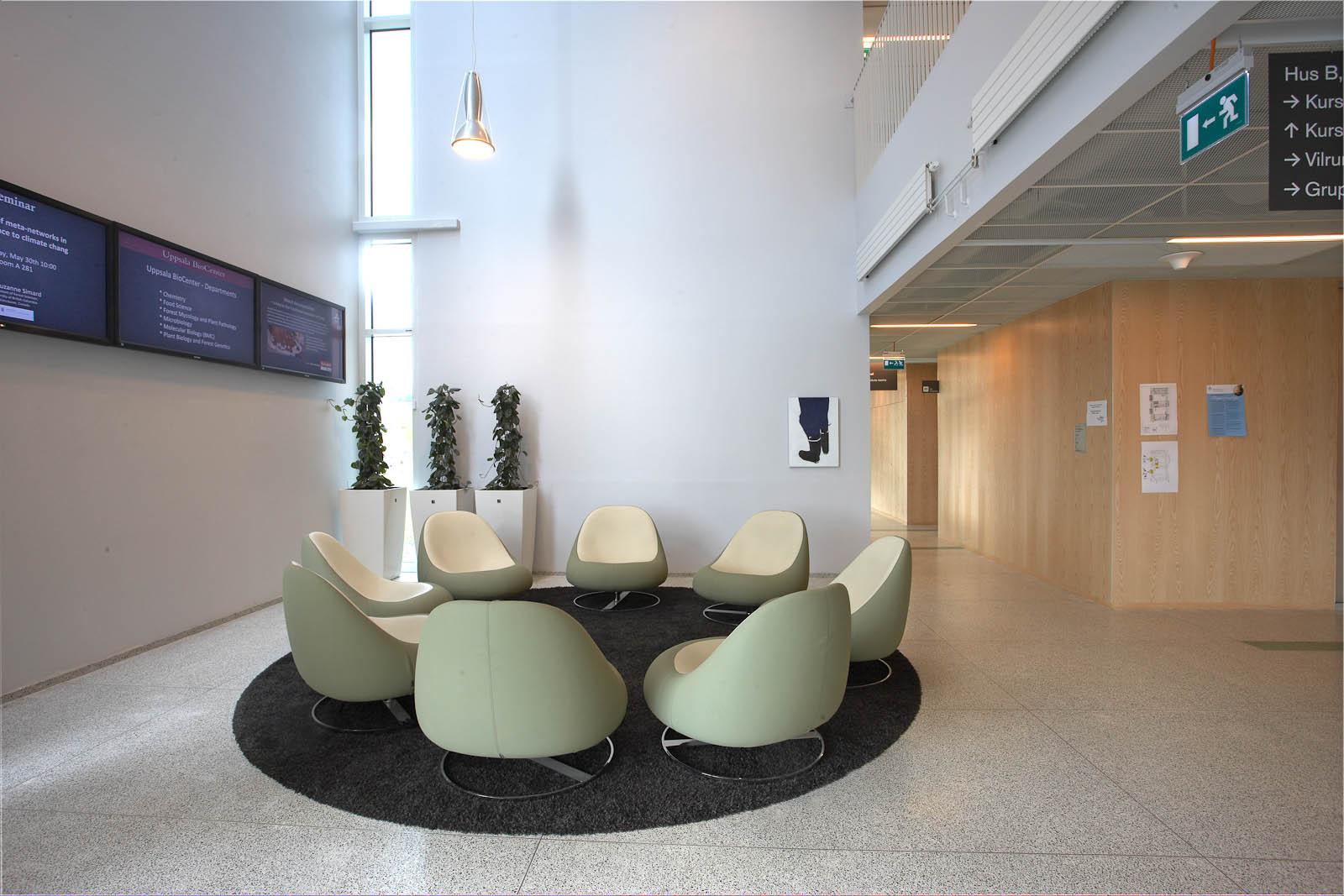 Soffgrupp med gröna fåtöljer i en vestibul. I bakgrunden på ena väggen en tavla med ett par blåklädda ben och svarta stövlar på vit bakgrund. Robert Lucander, 13 målningar