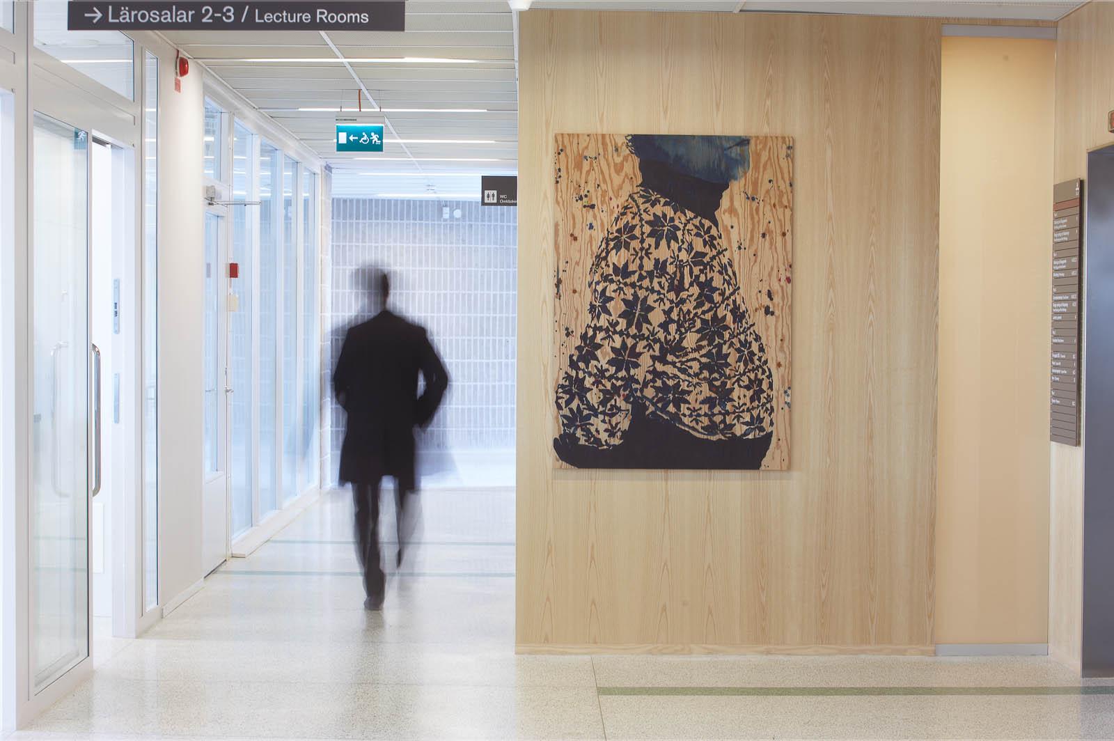 En person rör sig genom en korridor. På en trävägg hänger en tavla med en korpulent överkropp i mönstrad polokofta, målad på trä. Robert Lucander, 13 målningar