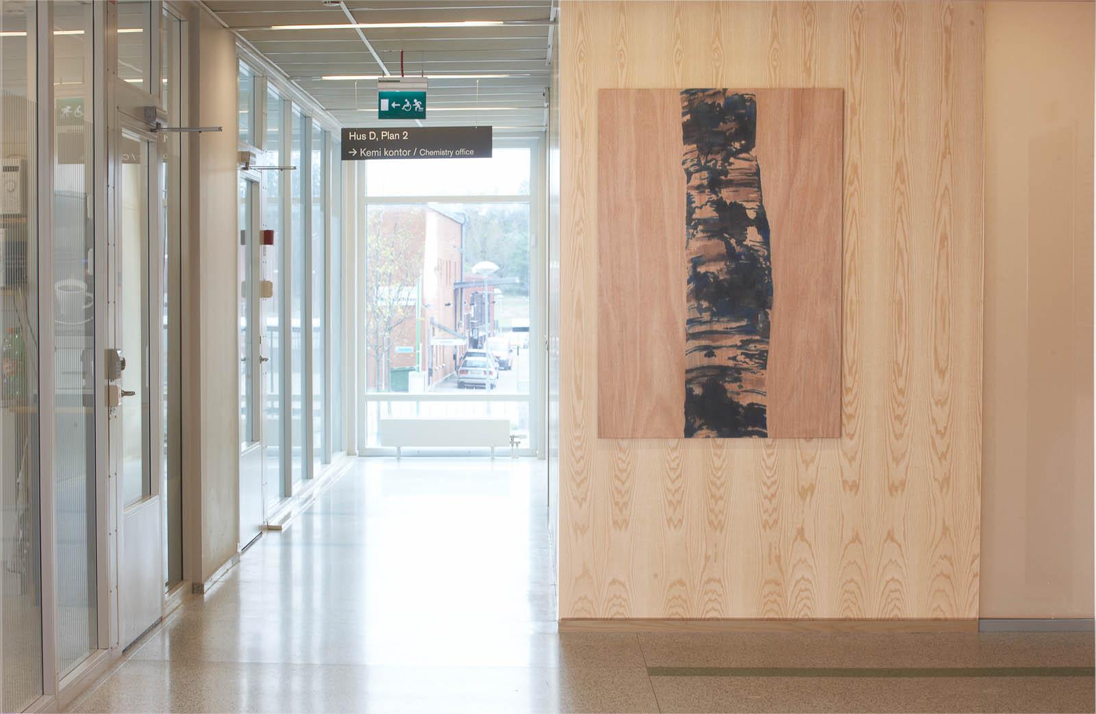 Korridor och trävägg varpå det hänger en tavla av en björkstam, målad på trä. Robert Lucander, 13 målningar