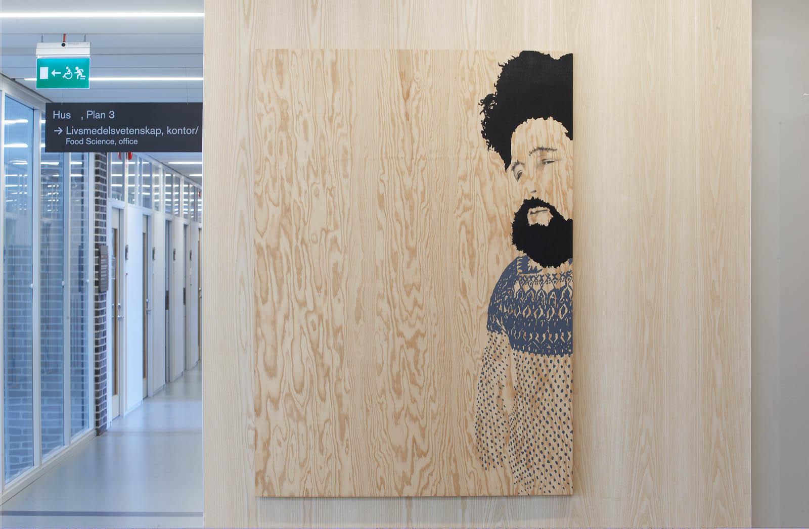 Korridor och trävägg med tavla målad på trä, av en man i kofta med kraftigt hår och skägg. Robert Lucander, 13 målningar