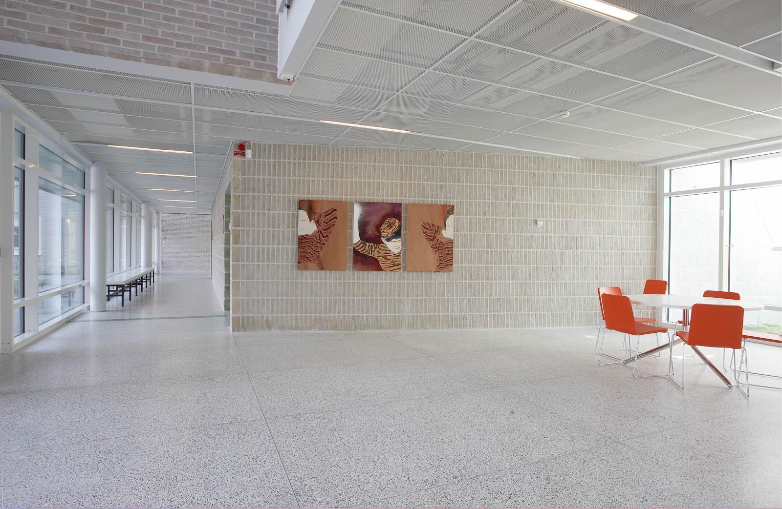 Korridor och en tegelvägg med tre tavlor i bredd av personer i randiga tröjor. Två av dem ler, den tredje har en randig mössa. Robert Lucander, 13 målningar