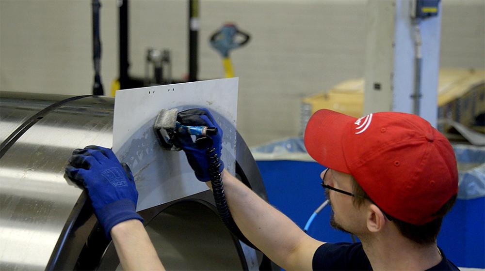 En man i keps och arbetshandskar skriver på ett papper vid en maskin av metall.