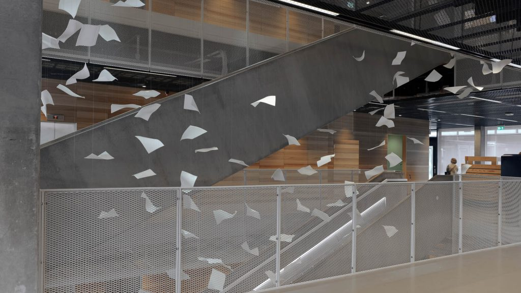 Ett stort antal virvlande pappersark i luften i trappvalvet på Studenthuset. Gabriel Lester, Twirl