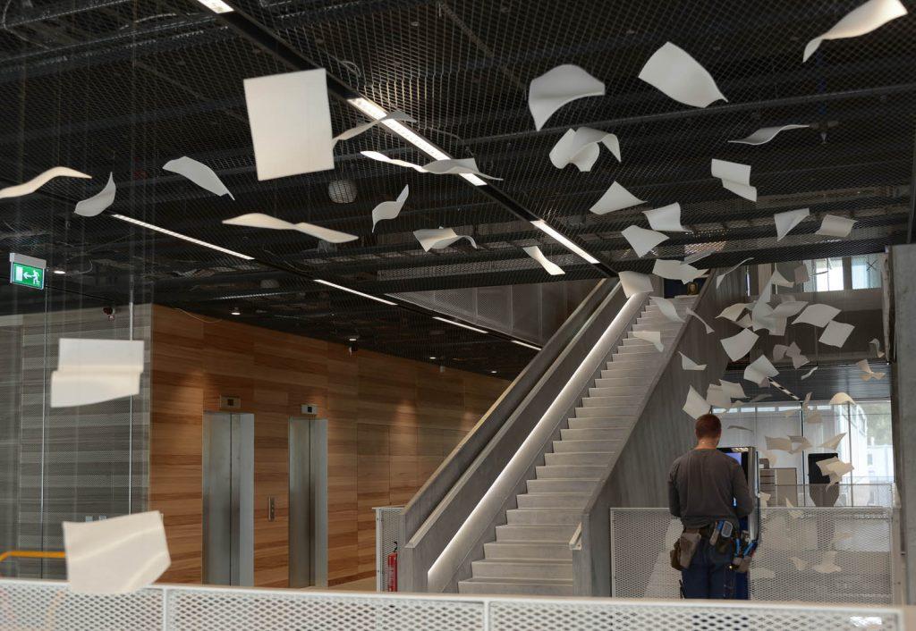 Virvlande pappersark i luften i entrén. Gabriel Lester, Twirl