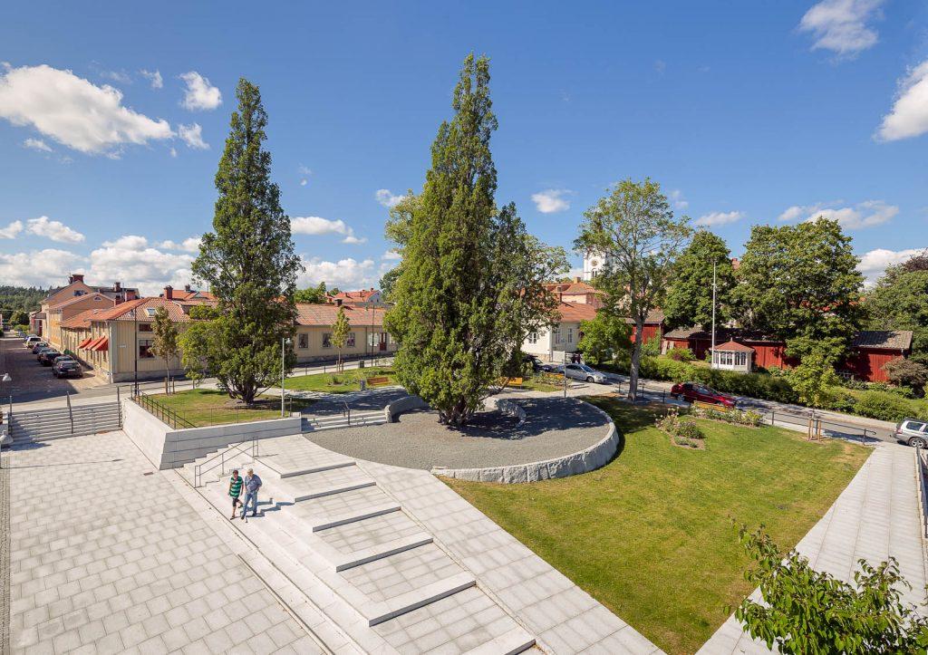 Liten stadspark med träd, gräsmatta och en cirkulär mittplätt av asfalt. Runtomkring finns bilvägar och hus. Magnus Carlén och Karin Tyrefors, Resecentrum i Nora, 2013