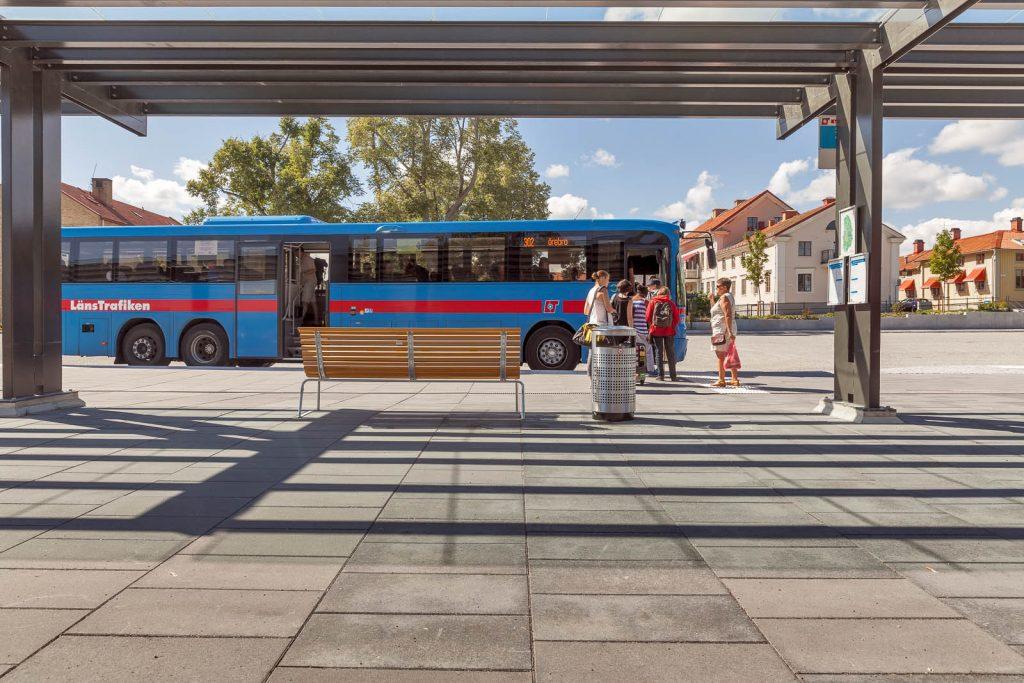 En blå buss står vid perrongen och människor kliver ombord. Magnus Carlén och Karin Tyrefors, Resecentrum i Nora, 2013