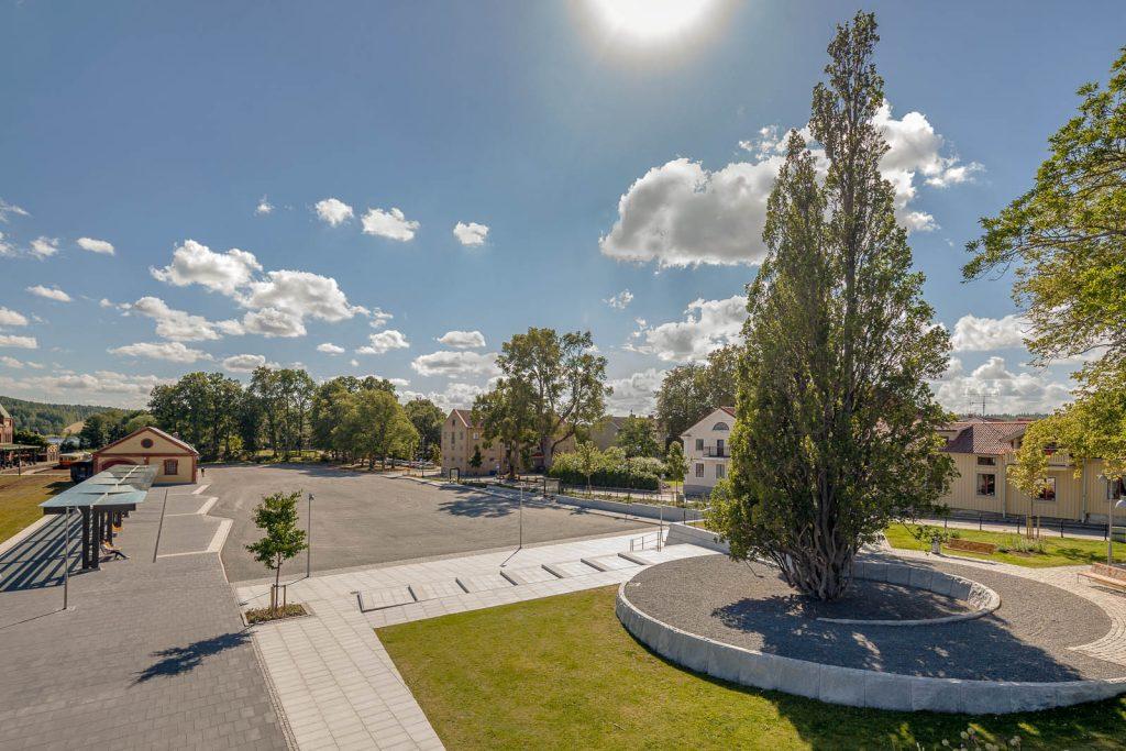 I anslutning till perrongen med glastak och bänkar ligger en liten stadspark med träd, gräsmatta och en cirkulär mittplätt av asfalt. Magnus Carlén och Karin Tyrefors, Resecentrum i Nora, 2013