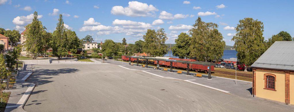 Väntplats utomhus med glastak och bänkar mellan järnväg och asfaltväg. På ytterspåret står röda godsvagnar. Magnus Carlén och Karin Tyrefors, Resecentrum i Nora, 2013