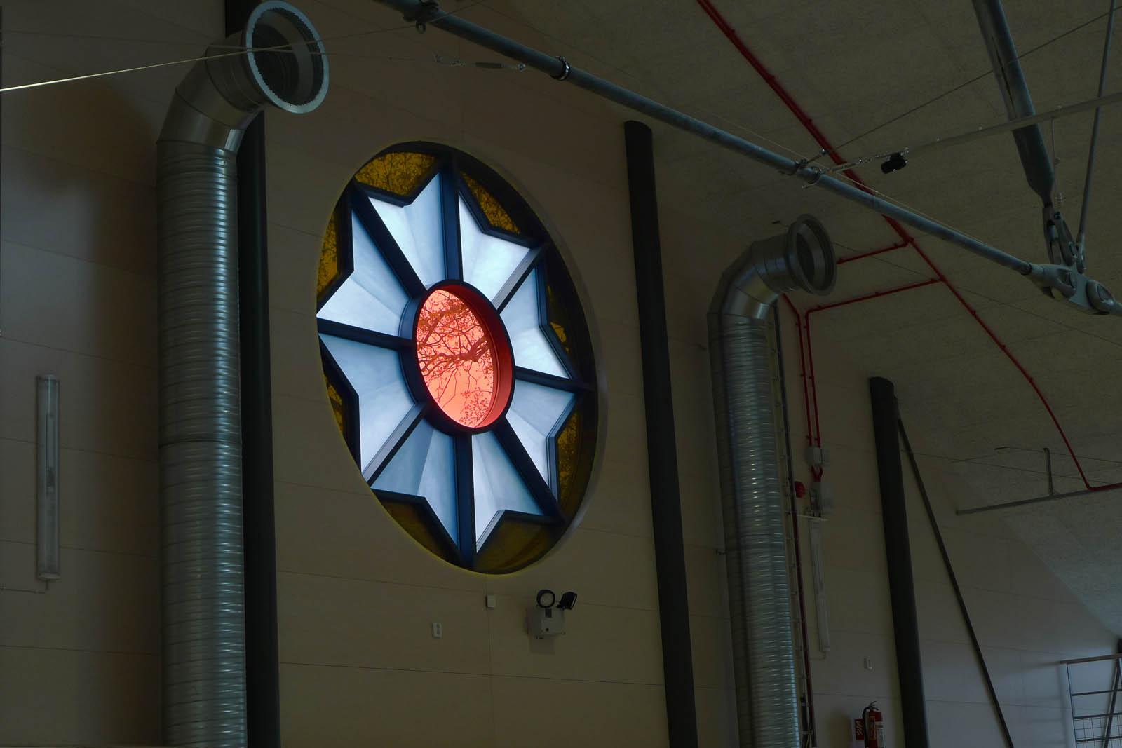 Två fönster, tre meter i diameter, med digitaltryckt, laminerat glas. Motivet är en kokard, prisrosett. Cecilia Aaro och Matilda Fahlsten, Kokard, 2014.