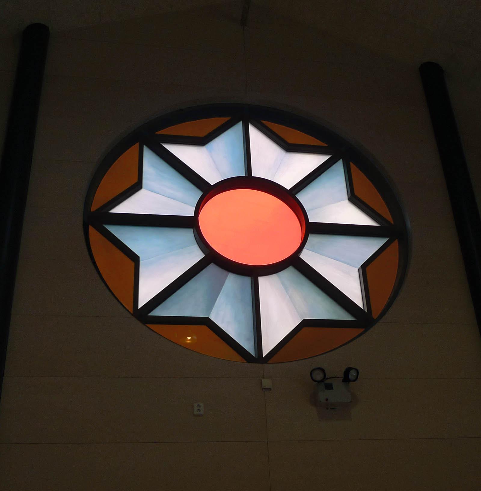 Ett cirkulärt fönster, tre meter i diameter, med digitaltryckt, laminerat glas. Motivet är en kokard, prisrosett. Cecilia Aaro och Matilda Fahlsten, Kokard, 2014.