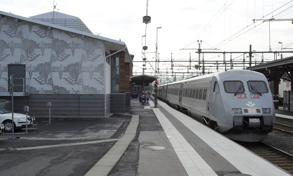 Ett tåg står inne. Passagerare rör sig på perrongen. Bredvid gaveln av ett hus med verket på. Karin Laaja, Unga män och järnväg