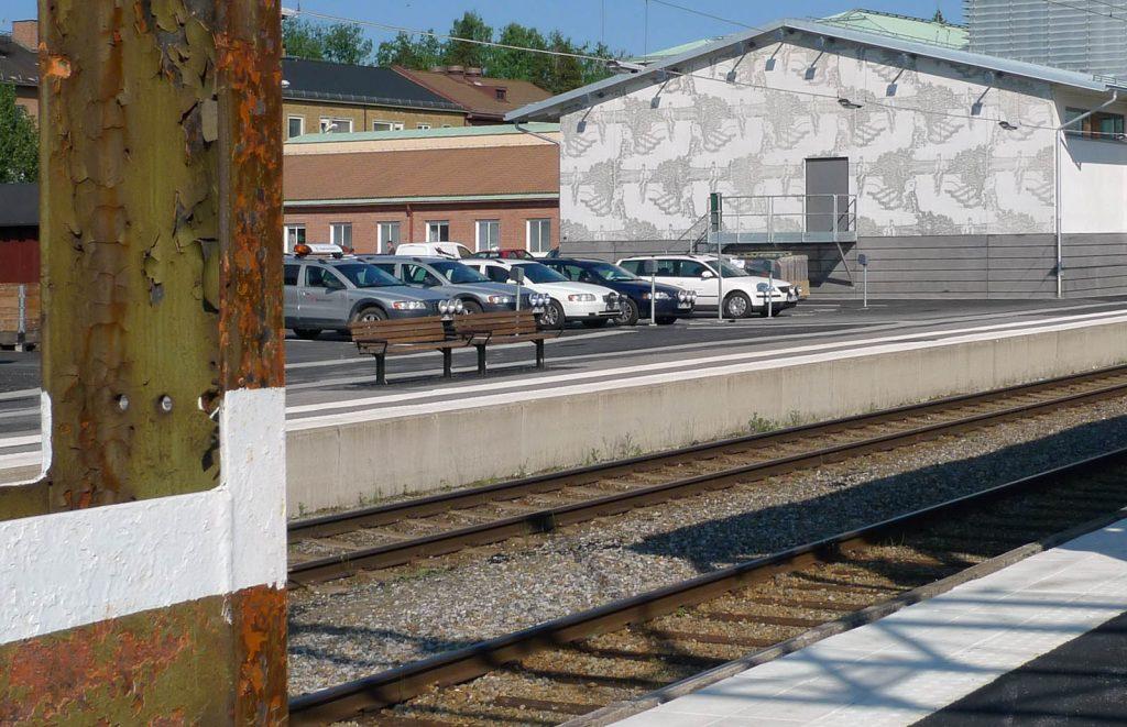 Verket med husgaveln vetter mot en parkering och mot tågspåret. Karin Laaja, Unga män och järnväg