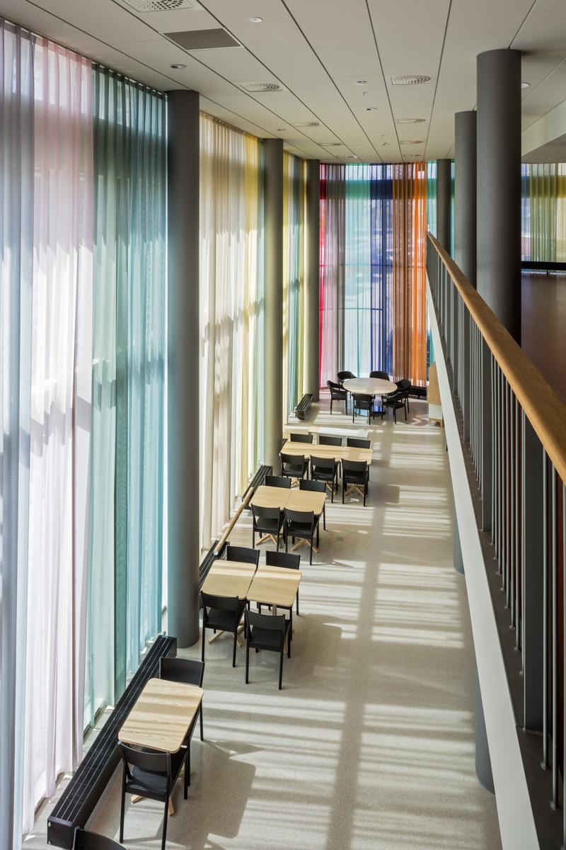 Korridor med stolar och bord. Ena väggen är täckt från golv till tak av ett flerfärgat draperi som släpper igenom ljuset utifrån. Astrid Krogh, Layers of Colour and Light