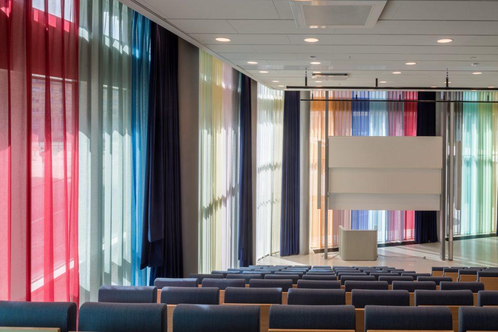 En hörsal med högt i tak och rader av stolar framför ett podium. Ytterväggen är täckt av ett mångfärgat draperi som släpper igenom ljuset utifrån. Astrid Krogh, Layers of Colour and Light