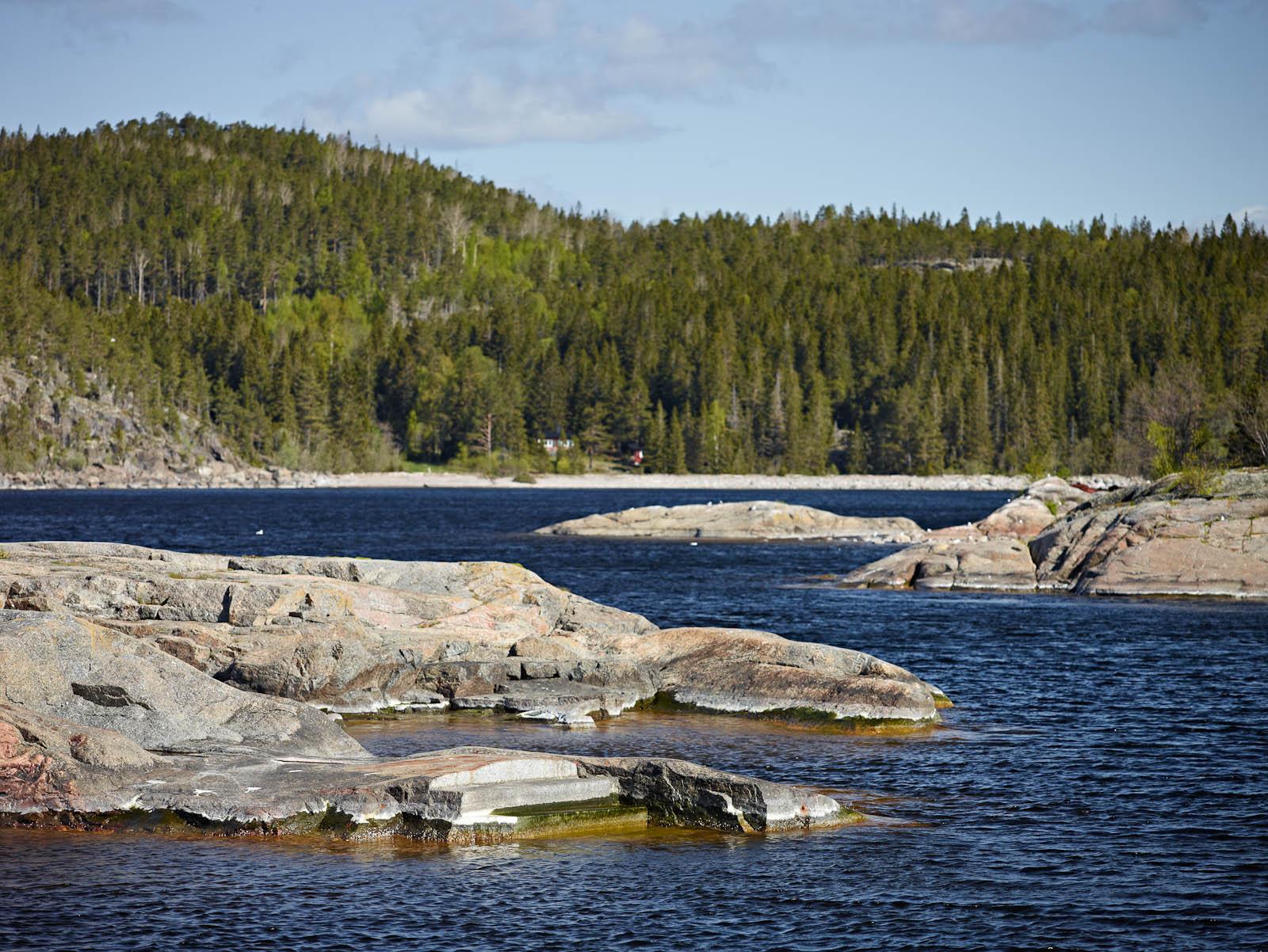 Klippstrand med två trappsteg och strömmande vatten. I bakgrunden gröna tallar. Katarina Löfström, Passage