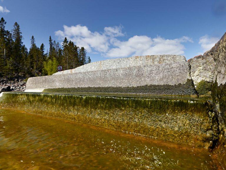 Två trappsteg inhuggna i klippan, det nedre fuktigt och grönt av mossa. Nedanför strömmar vattnet och döljer nästa trappsteg. Katarina Löfström, Passage