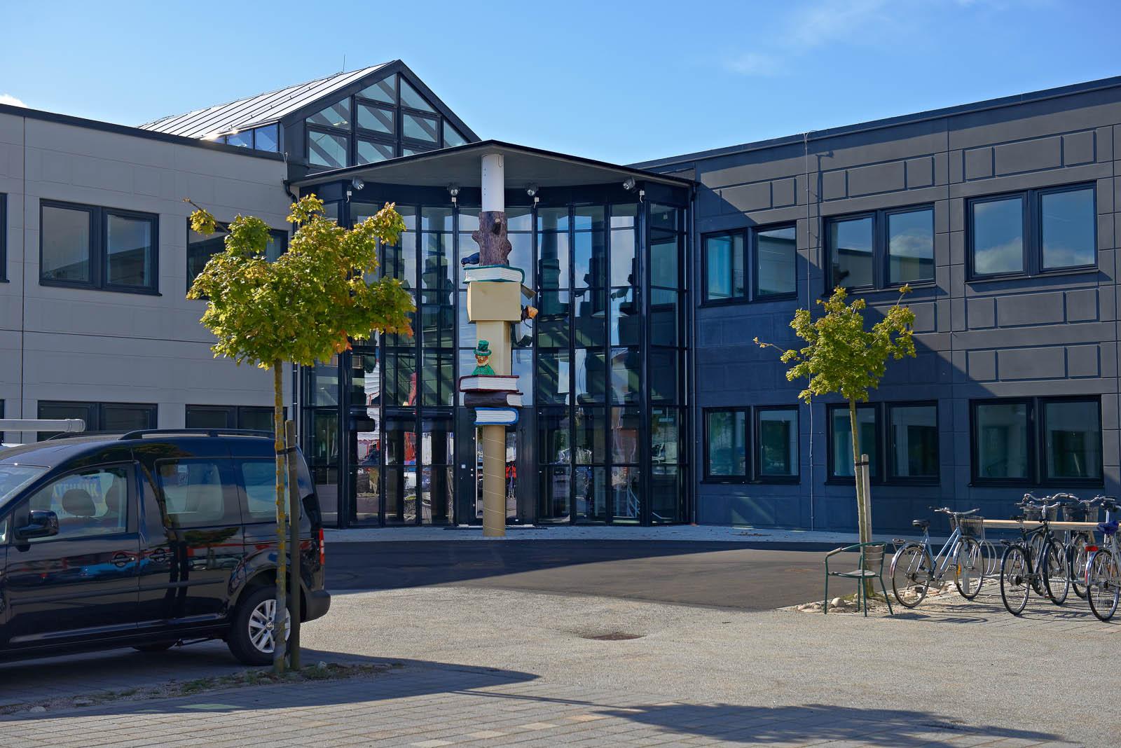 Framför byggnaden med pelaren ligger en parkeringsplats och ett cykelställ. Daniel Jensen, Fundamentet (2012)