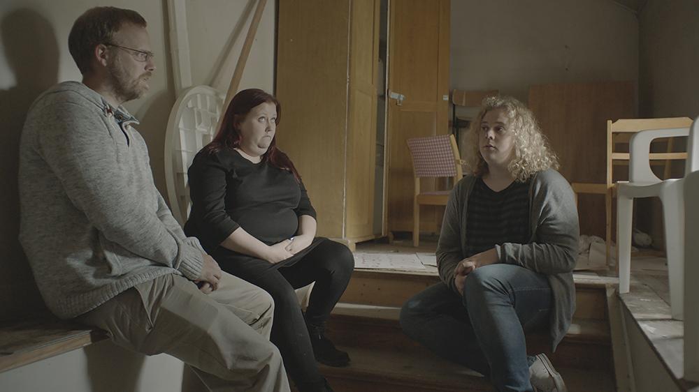 Två män tycks samtala. En kvinna ser sorgsen ut och tittar upp i taket. I bakgrunden utspridda möbler. Annika Eriksson, Övning inför ett psykodrama