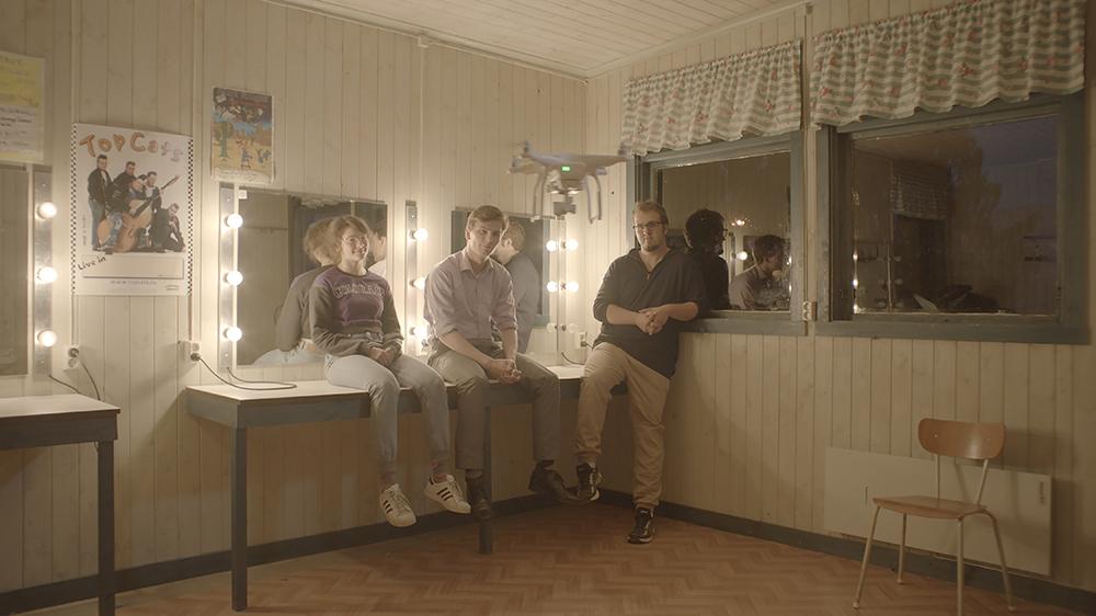 En kvinna och två män i ett rum i en timrad stuga. Längs väggen sminkbord med belysning kring speglarna. Personerna sitter på borden och tittar mot kameran. Annika Eriksson, Övning inför ett psykodrama