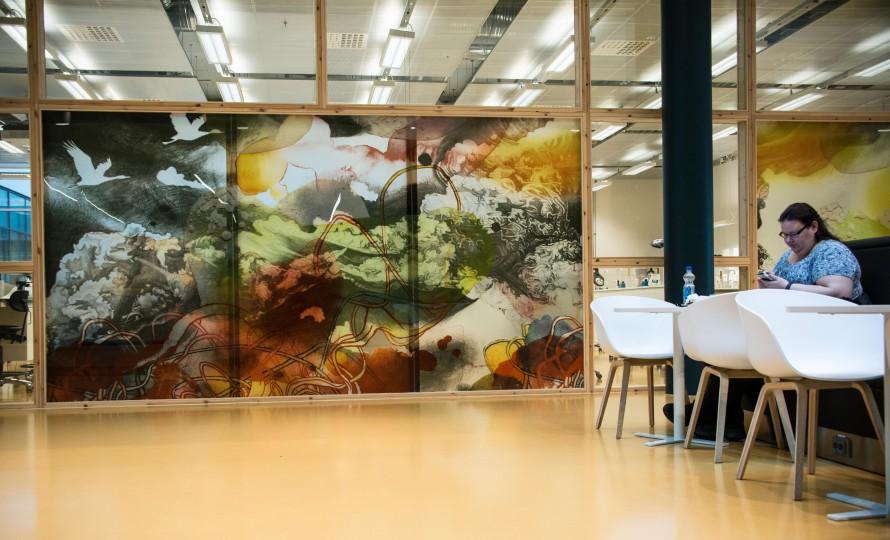 Stor målning på en glasvägg, med flygande fåglar och färgade formationer. Christoffer Paues, All Världens Djur