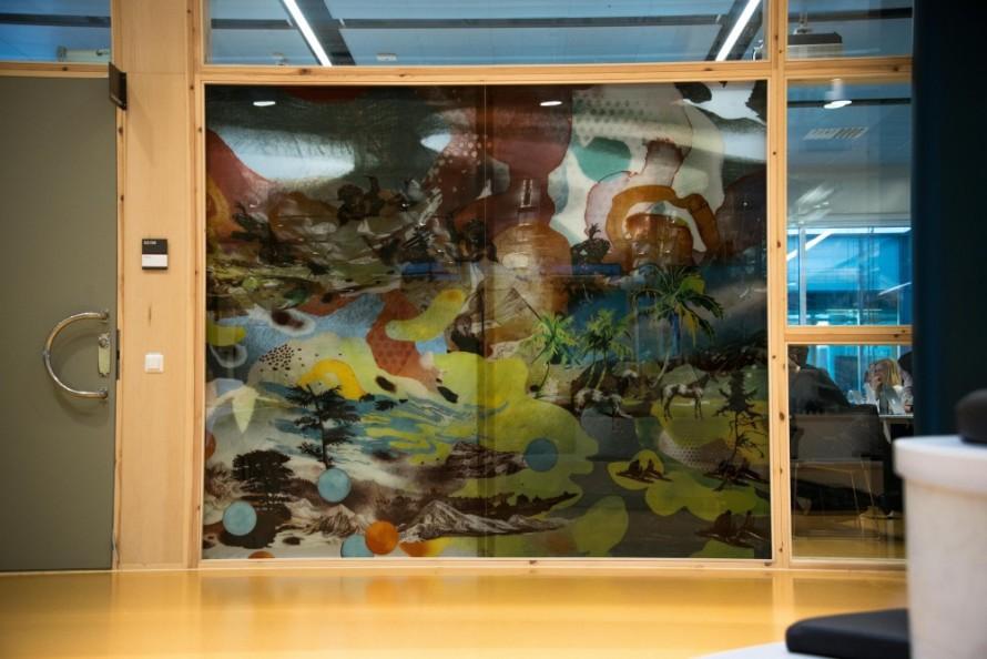 Färgglad målning på glasvägg, på andra sidan väggen skymtar studerande. Christoffer Paues, All Världens Djur