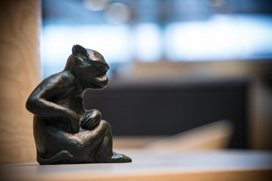 Skulptur av hopkrupen liten apa som kliar sig på magen. Christoffer Paues, All Världens Djur