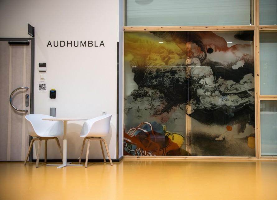 Två stolar och ett bord i en korridor bredvid en stor målning på en glasvägg, med färgade formationer. Christoffer Paues, All Världens Djur