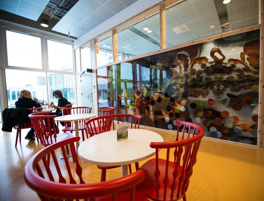 Flera vita bord med röda stolar framför en stor målad glasvägg med ett sagodjur på. Christoffer Paues, All Världens Djur