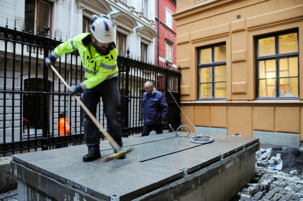 En man i arbetskläder förbereder sockeln där arken ska fästas. Jan Håfström Arken