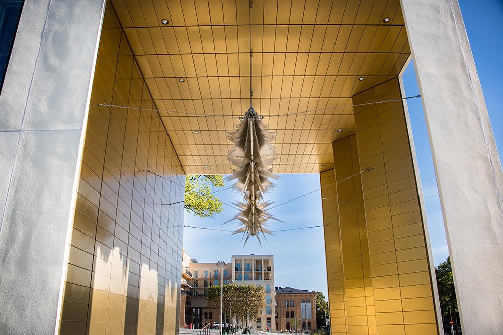 Ljudvågen i formskuren aluminium är fäst med vajrar i taket på den gulfärgade loggian. Ebba Matz, Sch, tyst, lyssna