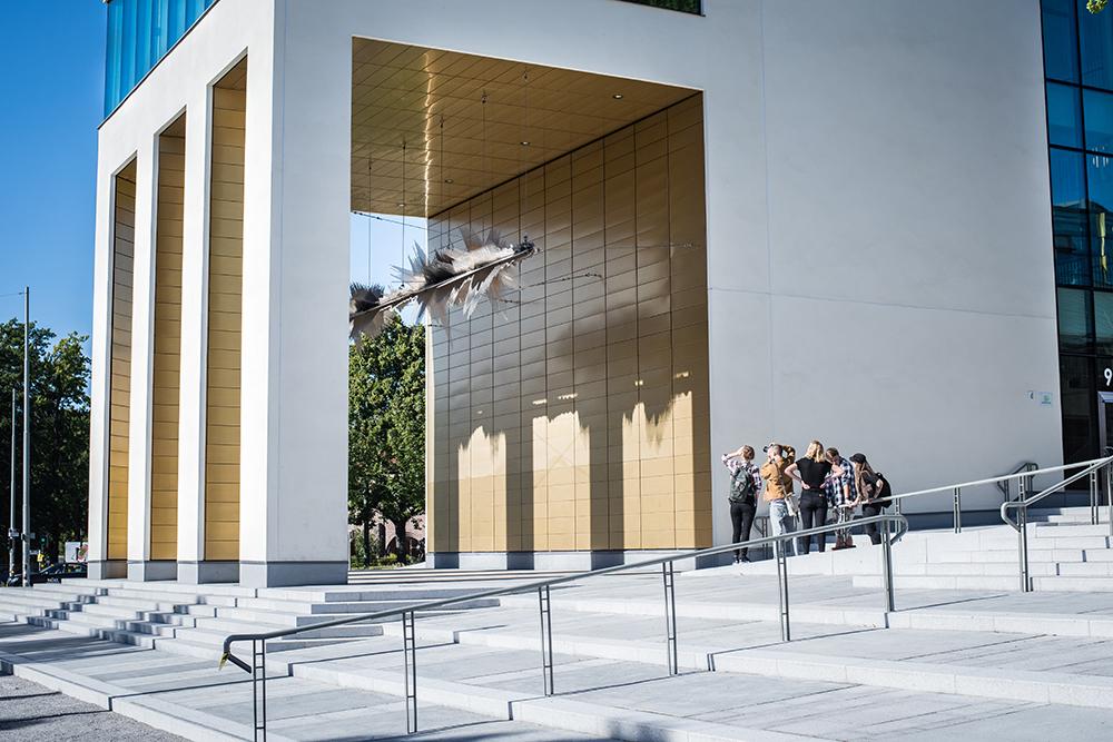 Skulptur som hänger i en guldfärgad loggia fotograferas av en grupp intresserade. Ebba Matz, Sch, tyst, lyssna