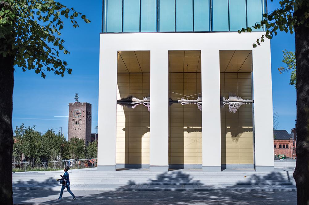 Man går förbi byggnad med vita pelare och en guldloggia där en skulptur hänger i loggian