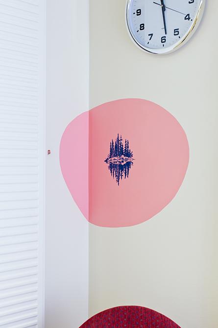 Skär rundel på väggen med en blå teckning av tallar som speglar sig i ett vatten. Gerd Aurell, Till mitten hunnen.