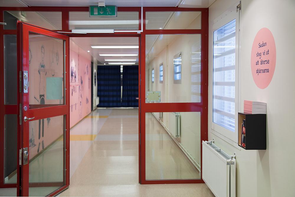 Innanför en öppen glasdörr är korridorens ena vägg skär och full med tecknade figurer. Gerd Aurell, Till mitten hunnen.