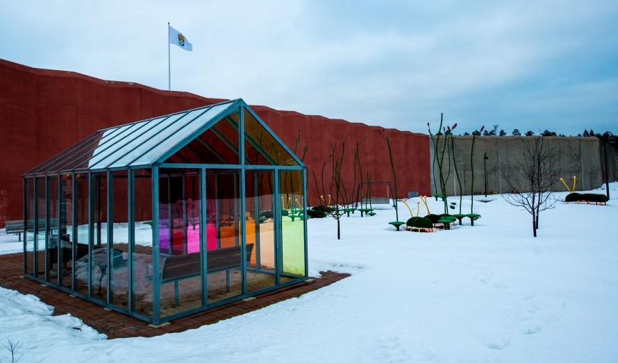 Litet växthus med olikfärgade glasväggar och snö på marken runtomkring. Thomas Nordström, Glänta, 2014