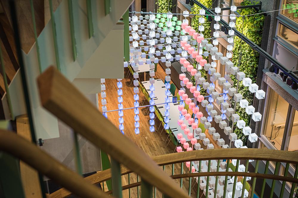 I ljusgården nedanför ett trappräcke hänger serier med kuber i olika färger monterade i lodräta och vertikala rader. Gustav Hellberg, XYZ