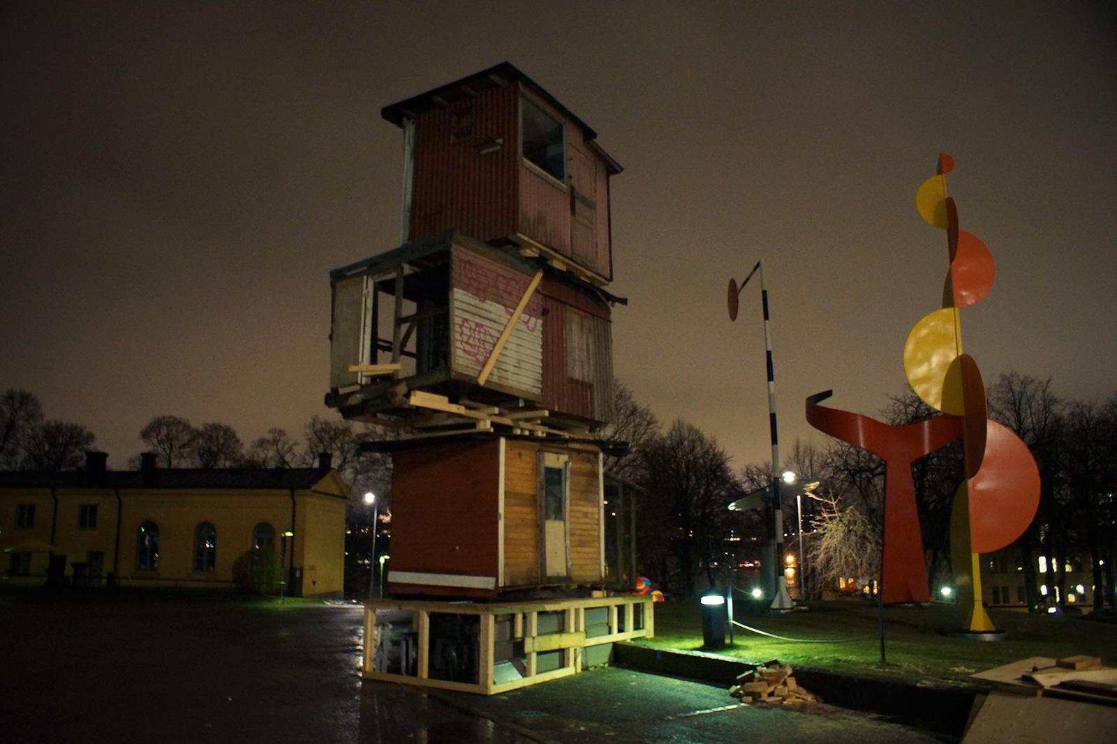 Tre slitna duvslag byggda av träplank, staplade ovanpå varandra utanför Moderna Museet i Stockholm. Simon Starling, Loft lift (stacked)