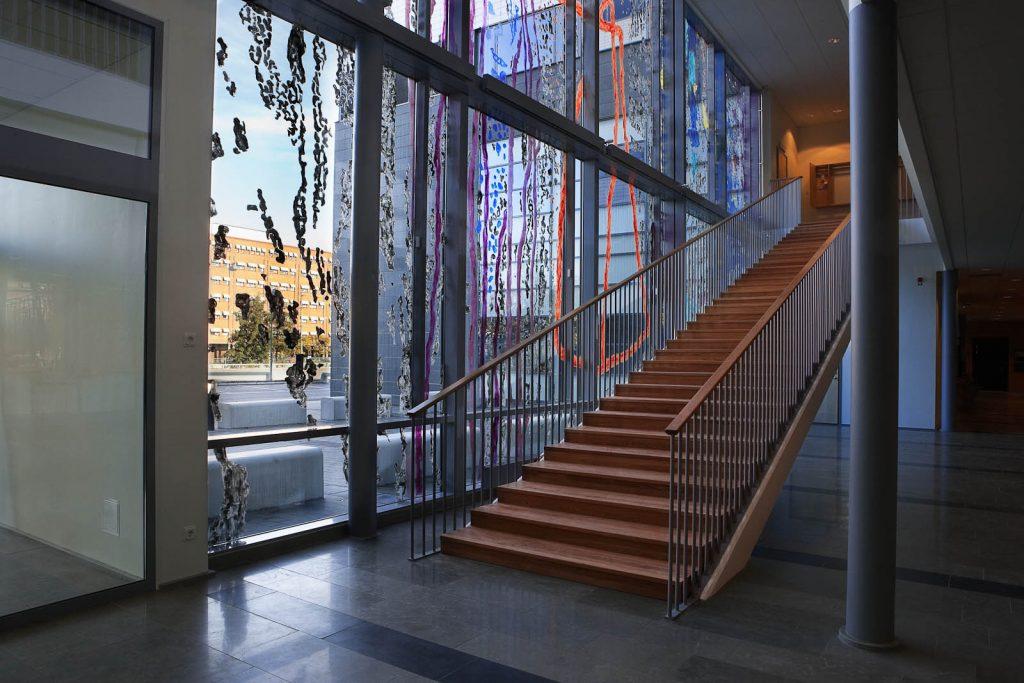 Trätrappa i entréhall nära glasfasaden. På glaset syns delar av målningen Vågen som ett raster i olika färger genom vilket man ändå kan se ut till gatan. Kåre Henriksson, Vågen