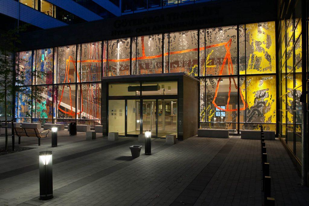Utifrån gatan syns den orangea vågen över ingången samt gula, blå och svarta partier, utspridda så att det fortfarande går att se genom glaset. Kåre Henriksson, Vågen