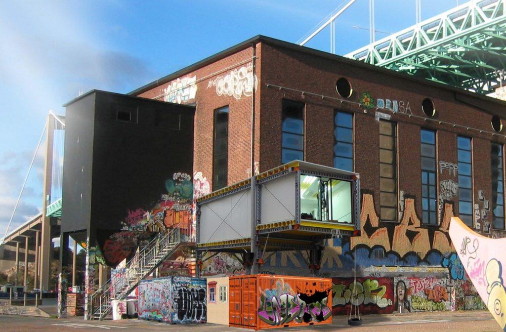 Tegelbyggnad med graffitimålningar. Framför den containrar och ovanför del av en metallbro. Santiago Cirugeda & Loulou Cherinet, How/Gibca