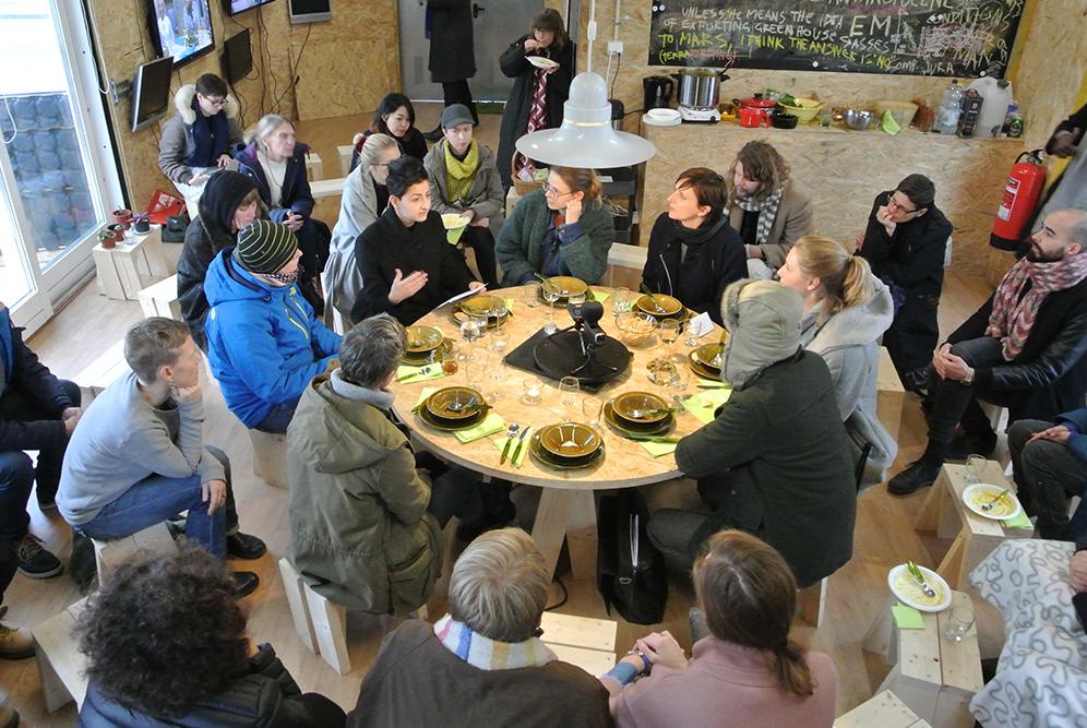 Människor kring ett dukat bord och folk på pallar runtomkring. På bordet en kamera. Alla lyssnar på en kvinna som talar. Santiago Cirugeda & Loulou Cherinet, How/Gibca.