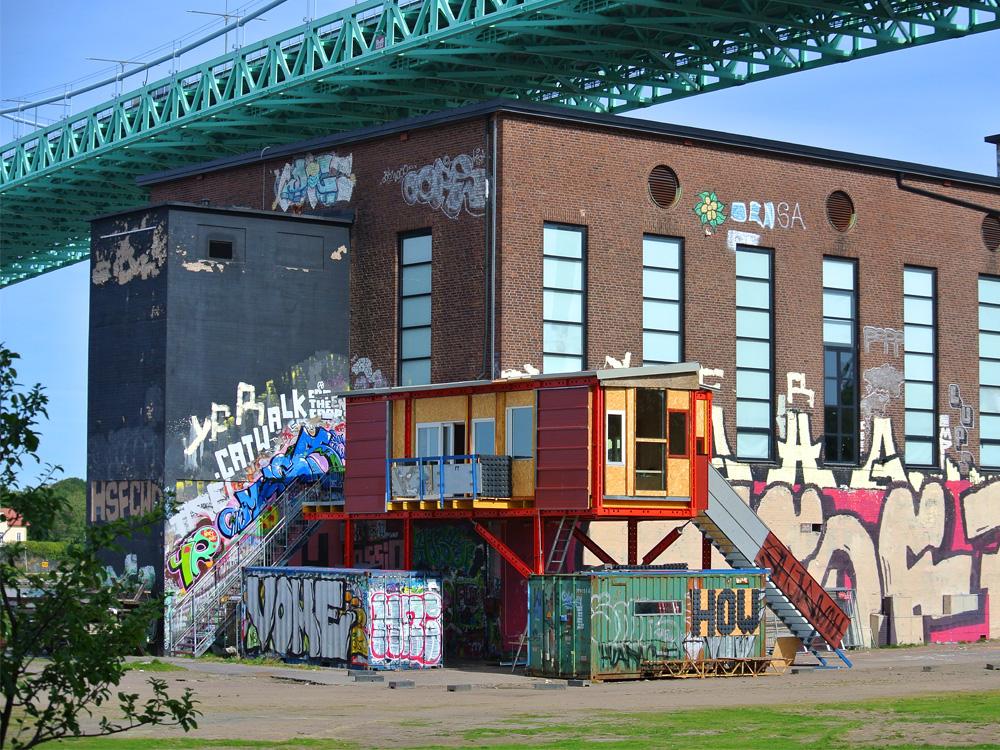 Graffitimålad tegelbyggnad. Framför den ett litet rött hus uppbyggt på röda balkar och med trappor till dörrarna. Santiago Cirugeda & Loulou Cherinet, How/Gibca