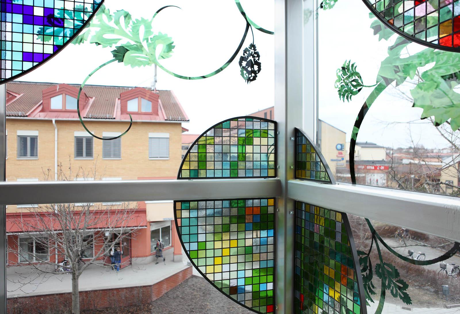 Glasruta med slingrande blommönster och en monterad skärm med bladformer i blyinfattat antikglas. Kristoffer Zetterstrand, In Vitro (2012)