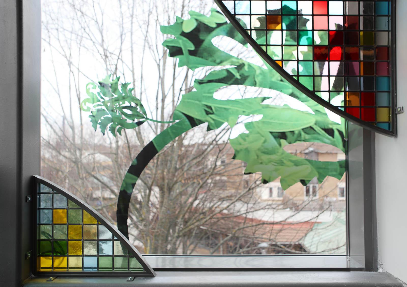 Glasruta med slingrande blommönster och monterade skärmar med bladformer i blyinfattat antikglas. Kristoffer Zetterstrand, In Vitro (2012)