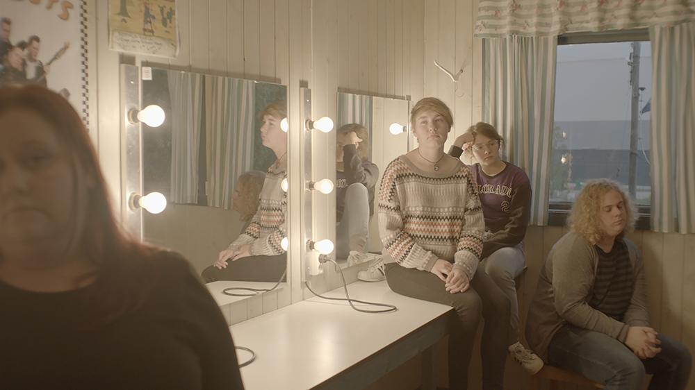 Tre kvinnor sitter i olika ställningar på sminkborden bredvid speglarna och ser ut mot rummet. En man sitter på en stol. Alla ser åt olika håll. Annika Eriksson, Övning inför ett psykodrama