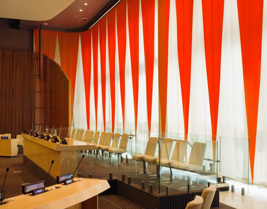 Åhörarstolar och bord med talarmikrofoner framför ridån. Ann Edholm, Dialogos, 2013