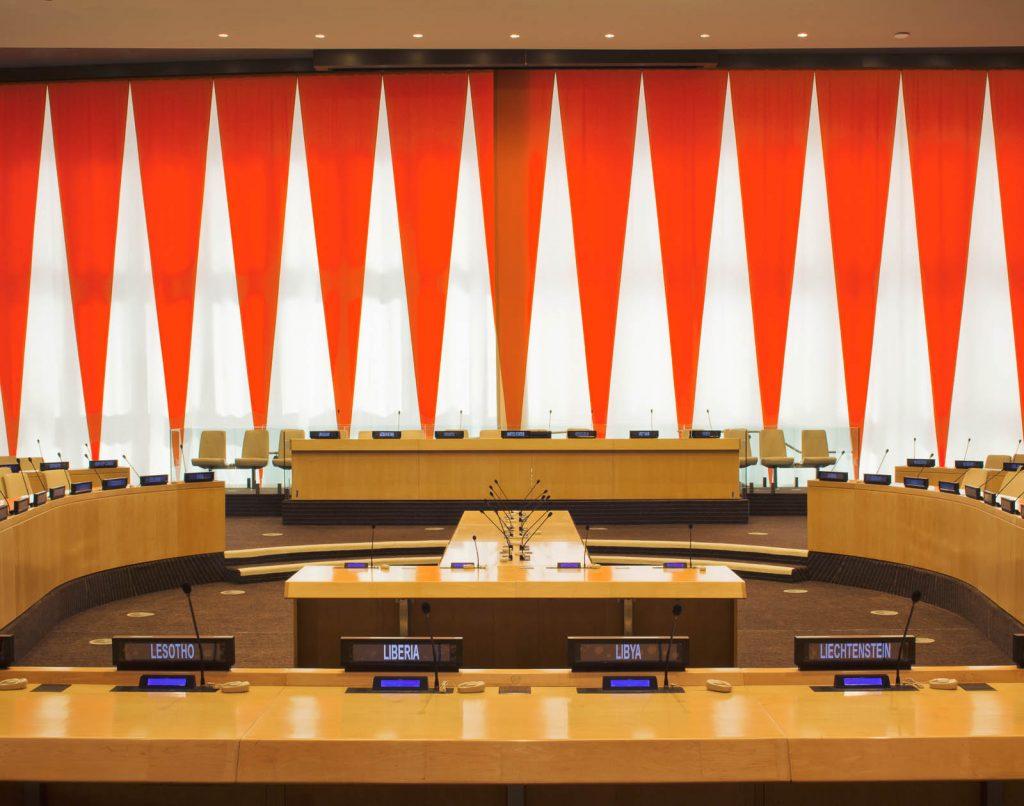 Podium med talarstolar, skärmar och mikrofoner, framför den rödvita ridån i ECOSOC-salen. Ann Edholm, Dialogos, 2013