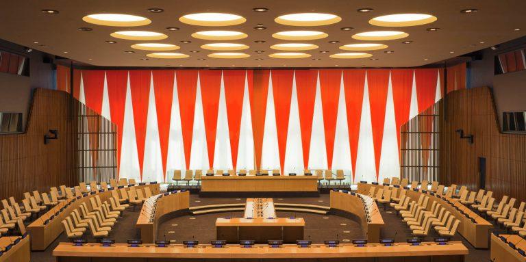 Den rödvita ridån täcker bakre väggen. I förgrunden podium med talarstolar, skärmar och mikrofoner, samt åhörarstolar. Ann Edholm, Dialogos, 2013