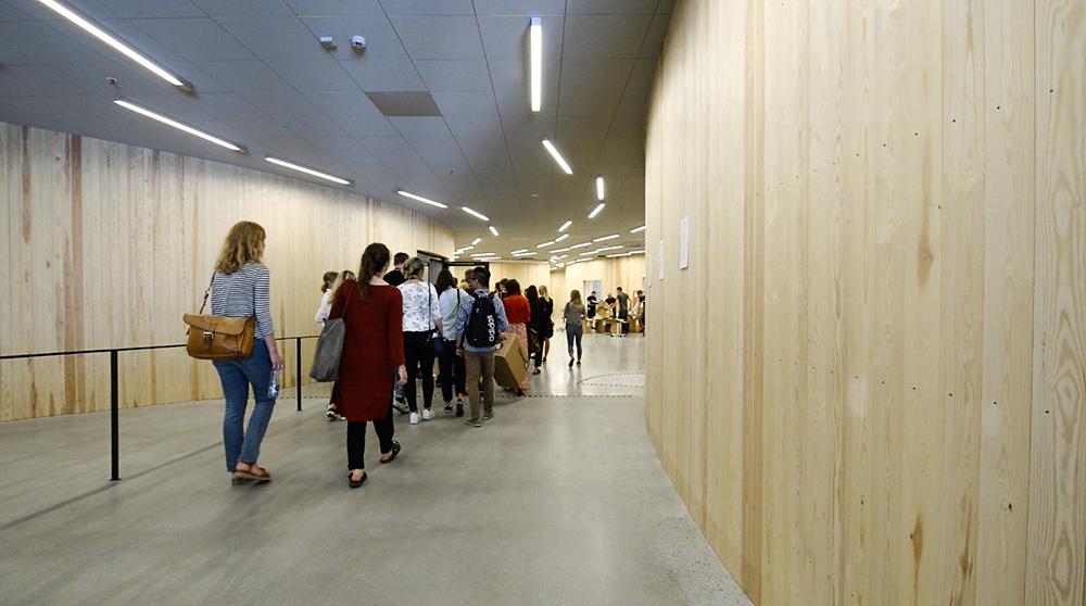 En grupp studenter går genom en korridor med träpanel och lysrör i taket. Jonas Dahlberg An imagined city