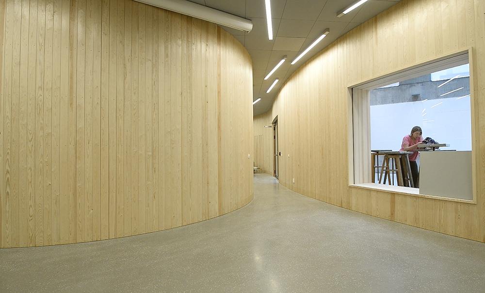Tom korridor med träpanel. En student syns genom ett fönster. Jonas Dahlberg An imagined city